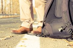 Feet and backpack of a male traveler or hitchhiker stock images