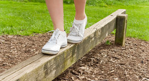 Feet balancing on a balance beam. A person is walking across a wooden balance beam Royalty Free Stock Photo