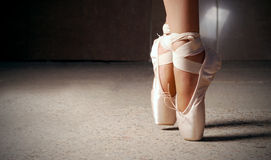Feet of ballerina dancing in ballet shoes. Over a dark background stock photos