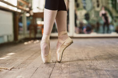 Feet of ballerina dancing in ballet shoes. Ballerina standing on toes royalty free stock photography