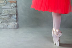 Feet of ballerina on pointe on concrete floor. Feet of ballerina on pointe on concrete grey floor royalty free stock photo