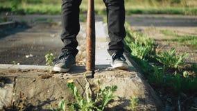 Feet and a baseball bat stands between your feet on the asphalt. Troublemaker