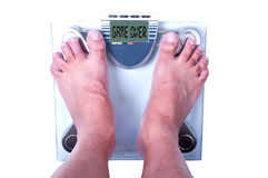 Feet on a bathroom scale. With the word game over! on the screen. Isolated Royalty Free Stock Photos