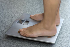 Feet on a bathroom scale. On grey stone floor Stock Image