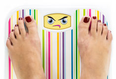 Feet on bathroom scale with angry cute face. On dial Stock Photo