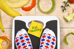 Feet on bathroom scale with Eat Healthy stock images