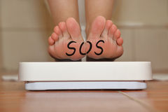 Feet on bathroom scale. With hand drawn SOS text Royalty Free Stock Photos