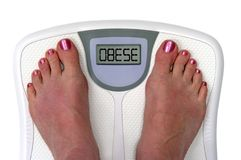 Feet on a bathroom scale - Isolated. Feet on a bathroom scale with the word obese on the screen. Isolated. Includes clipping path royalty free stock photos
