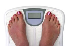 Feet on a bathroom scale - Isolated. Feet on a bathroom scale. Sceen is blank so you can enter your own numbers or text. Isolated. Includes clipping path stock image