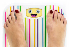 Feet on bathroom scale with laughing cute face Stock Photography