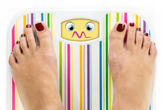 Feet on bathroom scale with overwhelmed cute face Stock Photo