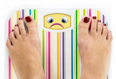 Feet on bathroom scale with sad cute face. On dial Stock Images