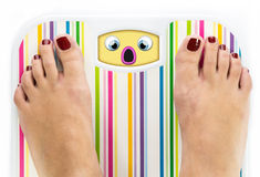 Feet on bathroom scale with scared cute face Royalty Free Stock Photos