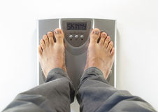 Feet on a bathroom scale skinny. Feet on a bathroom scale with the word skinny on the screen Stock Image