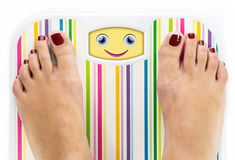 Feet on bathroom scale with smiling cute face Stock Photos