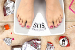 Feet on bathroom scale. With word SOS and junk food garbage Stock Photo