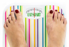Feet on bathroom scale. With words Eat smart on dial Stock Photo