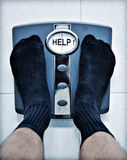 Feet Bathroom Scales Weight Loss Obesity. A man wearing socks weighing himself on bathroom scales with help on the dial stock image