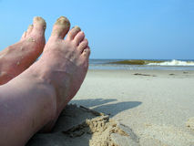 Feet on beach. Feet on a sandy beach with the ocean in the background Stock Image