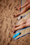 Feet on the beach. A couple tanning together on the beach, shot only their feet Stock Image