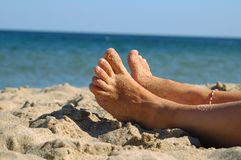 Feet on the beach. Feet of girl on the sandy beach at sunny day royalty free stock images