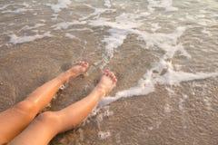 Feet on the beach. Child sitting on the sandy beach Royalty Free Stock Photo