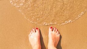 Feet on the beach. Female feet on the beach sand while relaxing Royalty Free Stock Photo
