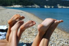 Feet at the beach in italy. The feet of three tanning girls on the beach in southern italy Royalty Free Stock Photos