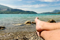 Feet on the beach of lake of Annecy Royalty Free Stock Photography