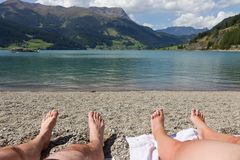 Feet on the beach, relaxing at the Reschensee Stock Photography