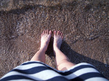 Feet on the beach. A woman stand on the beach in noon Royalty Free Stock Photography