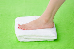 Feet of beautiful girl over white towel Royalty Free Stock Photography