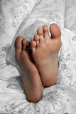 Feet in bed. Leisure time in bed with young boy's feet Stock Images