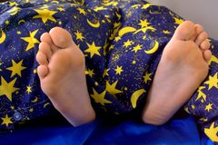 Feet in bed Stock Photography