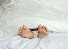 Feet are on the bed Royalty Free Stock Photos