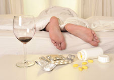 Feet on bed of sleeping man suffering hangover and Stock Photo