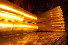 Feet of big Reclining golden Buddha statue Royalty Free Stock Images