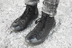 Feet in black gumshoes stand on gray ground. Teenager feet in black gumshoes standing on gray rough concrete floor Stock Photo