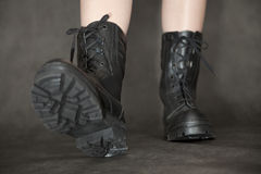 Feet in black leather army boots stock images