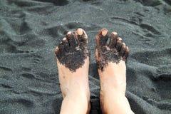 Feet in black sand range Royalty Free Stock Photography