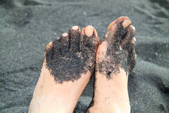 Feet in black sand range Royalty Free Stock Photos