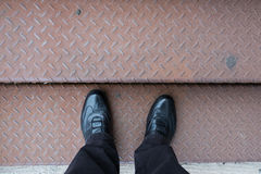 Feet with black shoes on rusty stairs Royalty Free Stock Photography