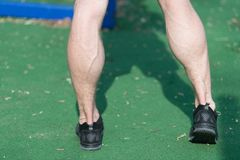 Feet in black sport fashion shoes on green grass. Muscular legs with veins at stadium or arena on sunny outdoor. Health and health. Y lifestyle. Sport training Stock Photo