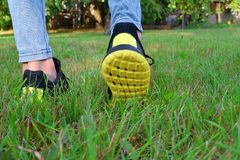 Feet in black yellow sneakers. Walking on green grass in park outside in summer day. Active lifestyle and recreation concept stock images