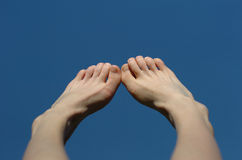 Feet on blue. Beautiful naked young female feet up to blue sky royalty free stock photos