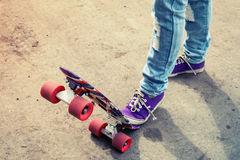 Feet in blue jeans and gumshoes on a skateboard Stock Photos