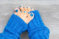 Feet with blue nails manicure. Women feet with blue nails manicure in blue socks royalty free stock photos
