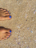 Feet with blue pedicure on the yellow sand beach, woman feet on the sandy beach Royalty Free Stock Photography