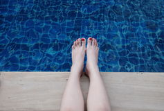 Feet in the blue pool Stock Images
