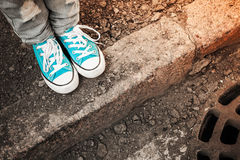 Feet in blue shoes stand on the street edge. Teenager feet in jeans and blue shoes stand on the street edge, urban walking theme. Vintage toned photo with retro Royalty Free Stock Photo